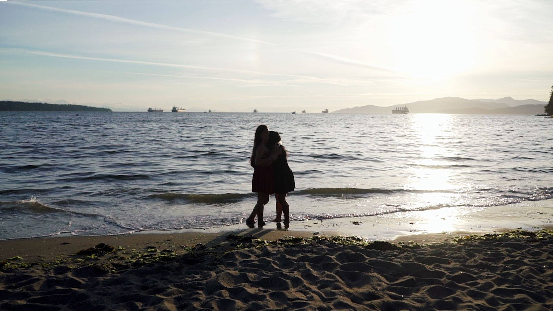 same sex couple embrace at 2nd beach vancouver