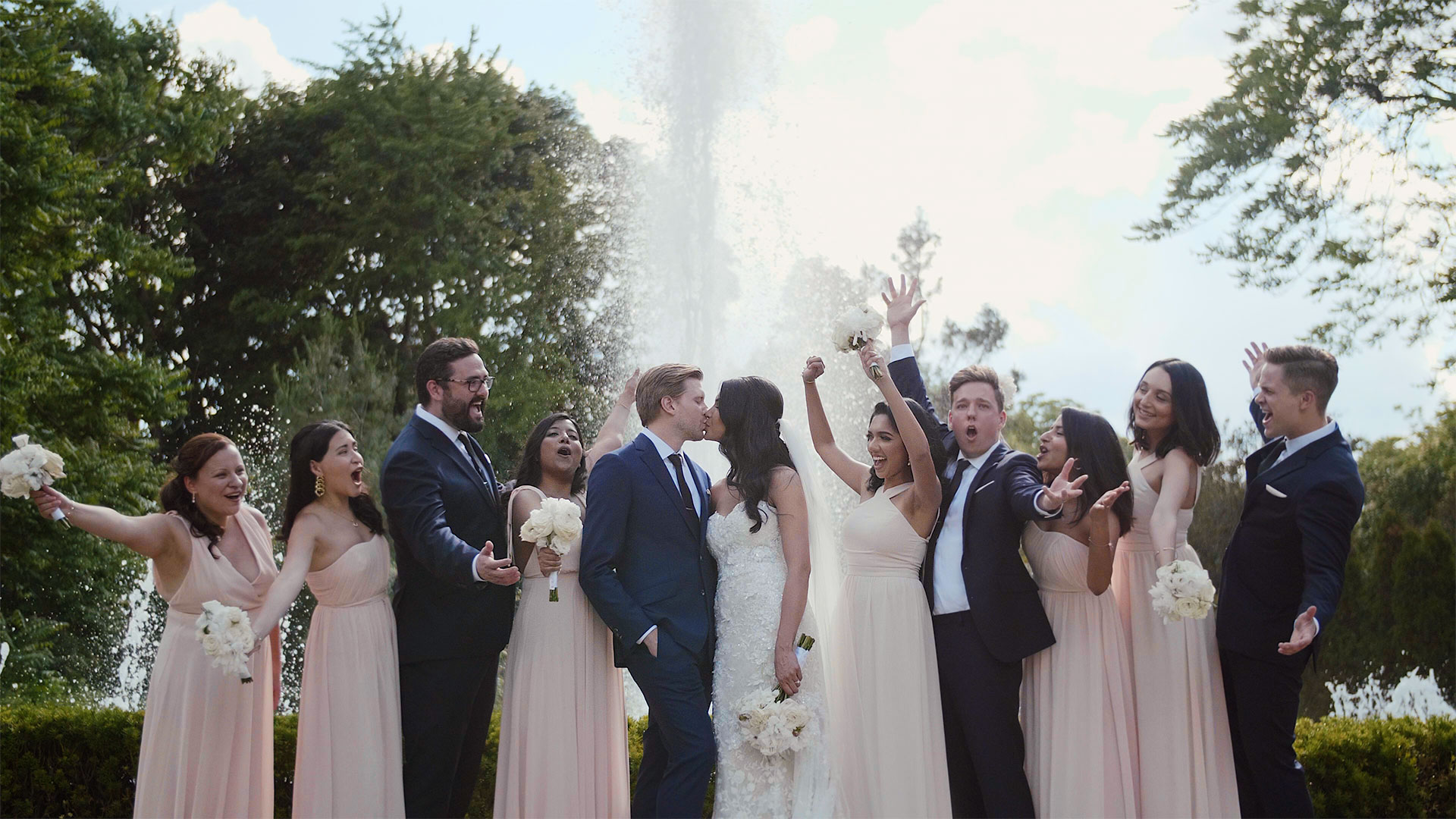 wedding party celebrating in front of fountain at Casa Loma wedding Toronto wedding videography by Kismet Creative