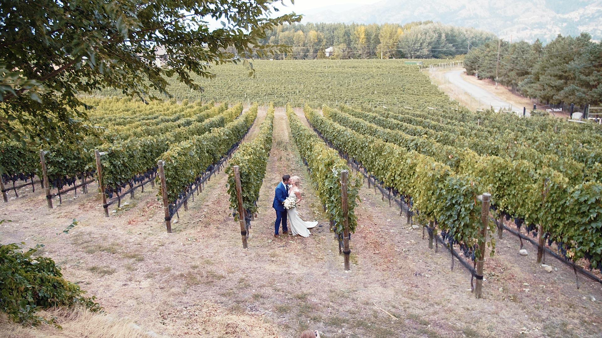 Bride and groom kissing at Kraze Legs Vineyard by Okanagan Wedding Videographer Kismet Creative