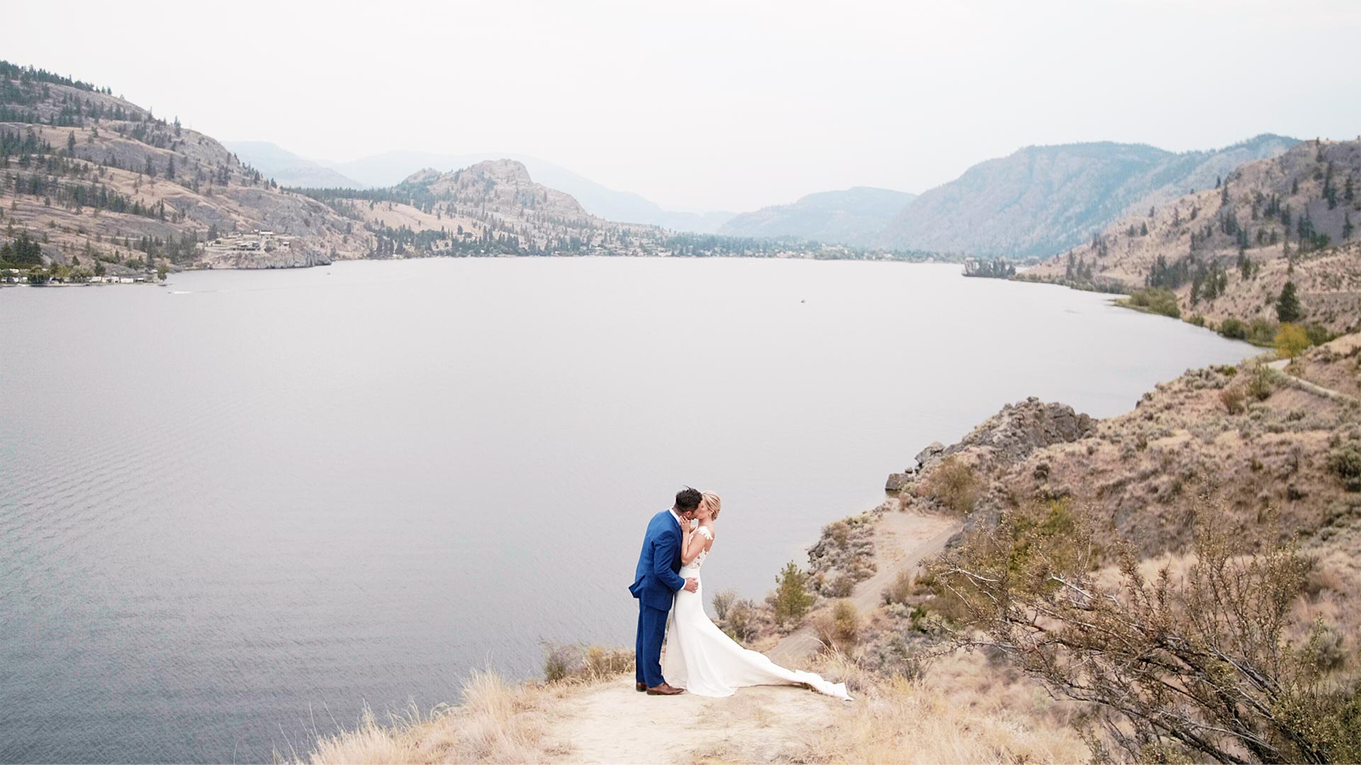 couple kiss on clifftop overlooking skaha lake by okanagan wedding videographer kismet creative
