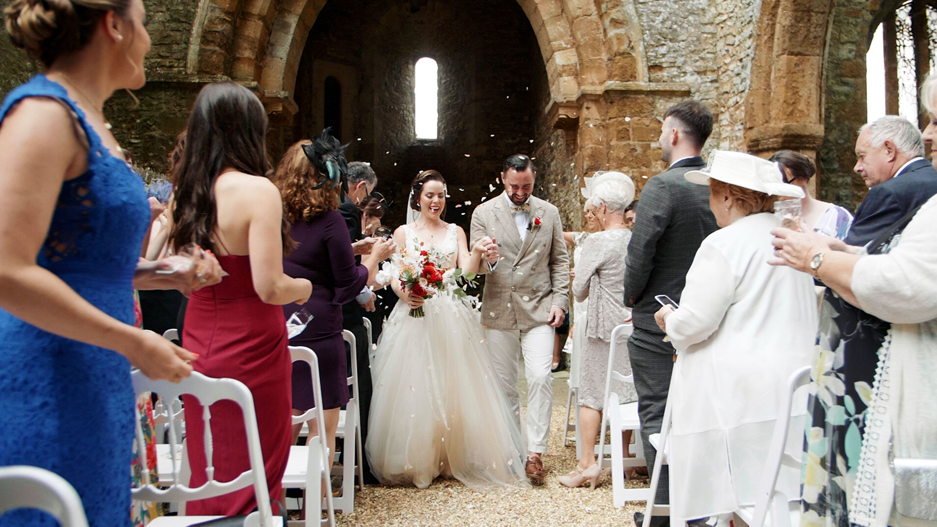 guests throw confetti over couple at their Ettington Park Hotel wedding by London wedding videogrpaher Kismet Creative