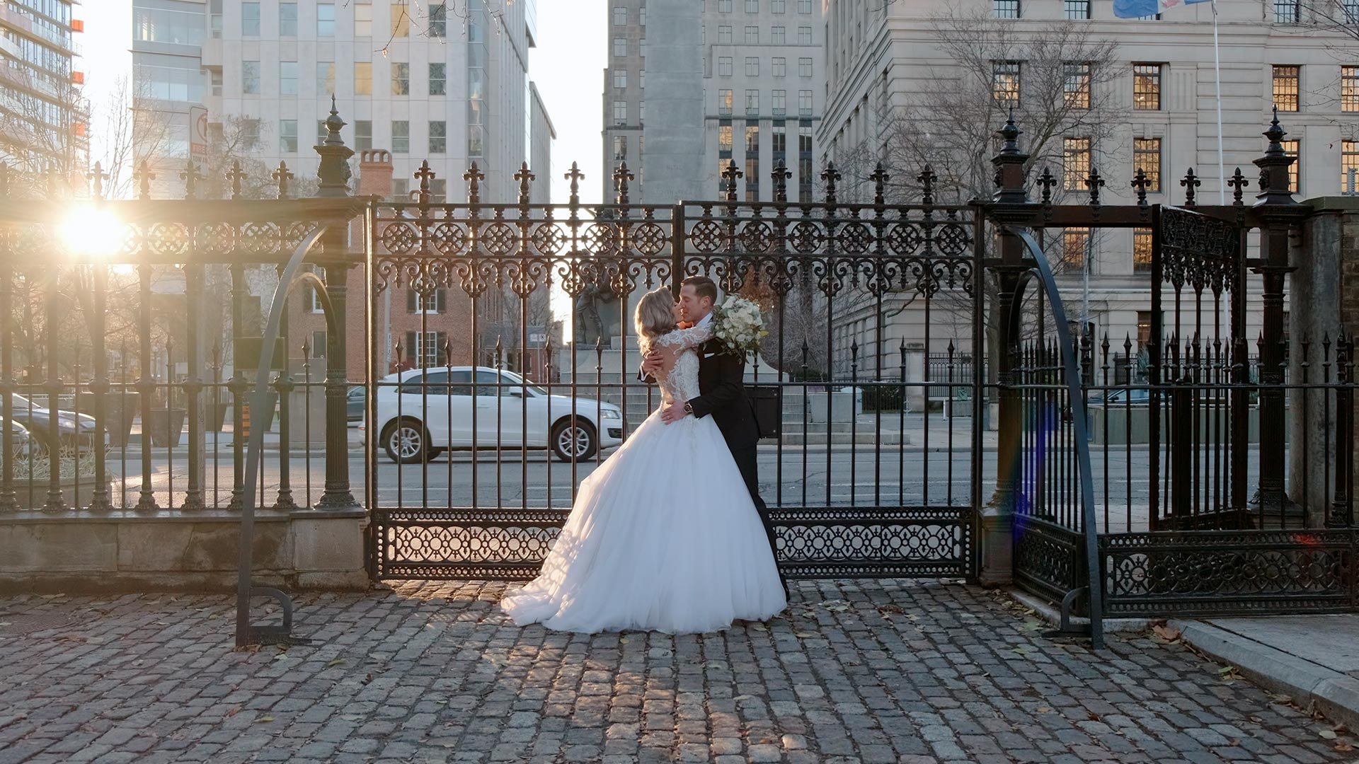 couple pose in front of gates as Osgoode Hall during their Micro Wedding in Toronto
