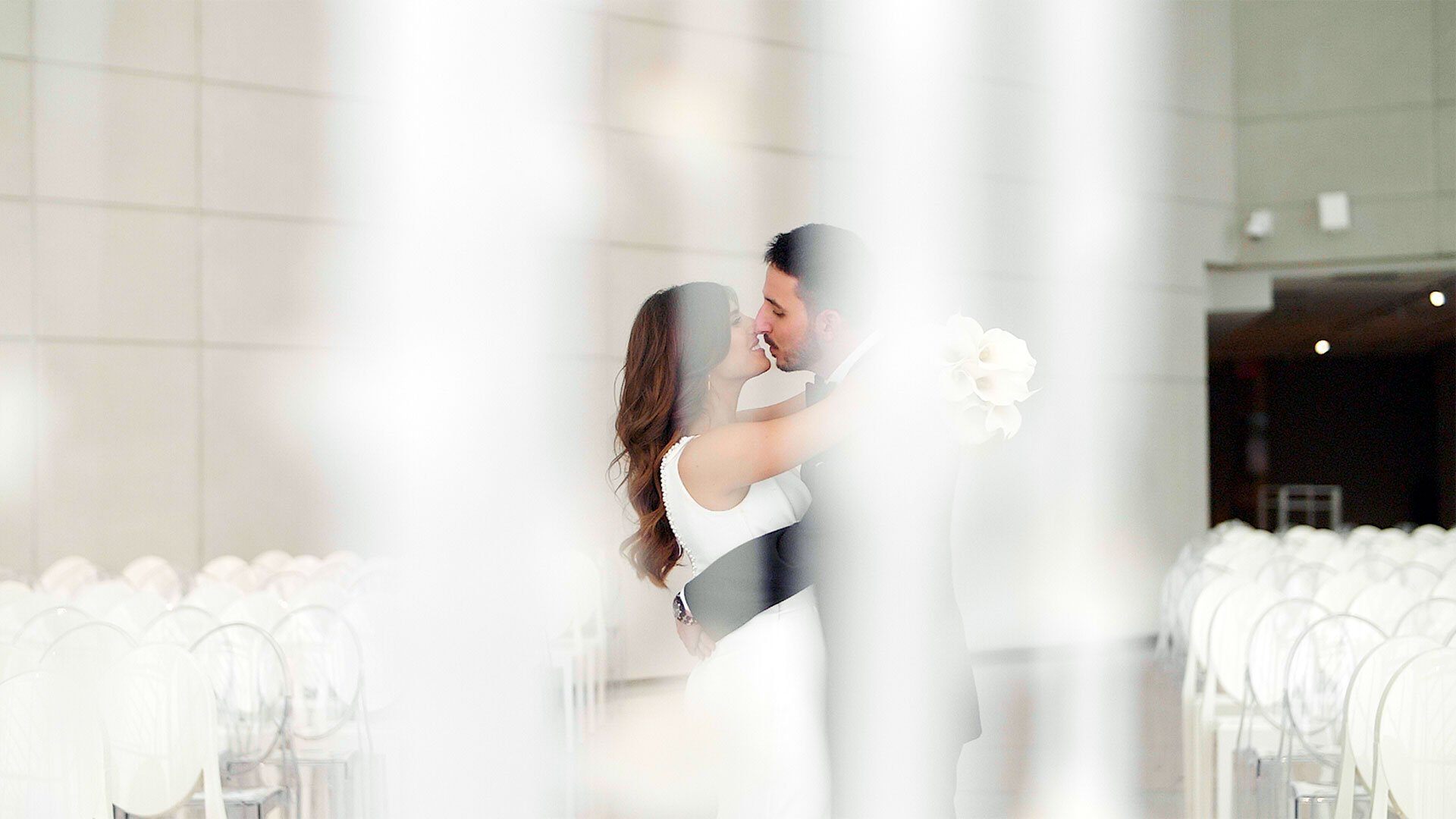 Bride and groom kiss in the New For Hall at the Hotel X Toronto
